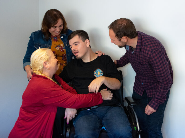 Man in wheelchair surrounded by loving family